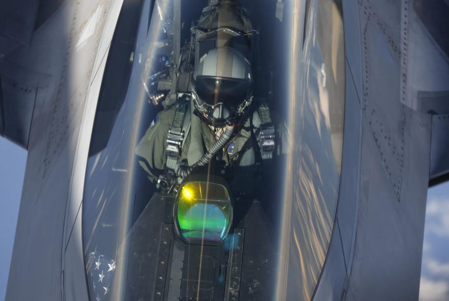The head-up display of a F-22 Raptor fighter jet reflects the sun light as a pilot of the 95th Fighter Squadron from Tyndall, Florida is seen during refuelling by a KC-135 Stratotanker from the 100th Air Refueling Wing at the Royal Air Force Base in Milde