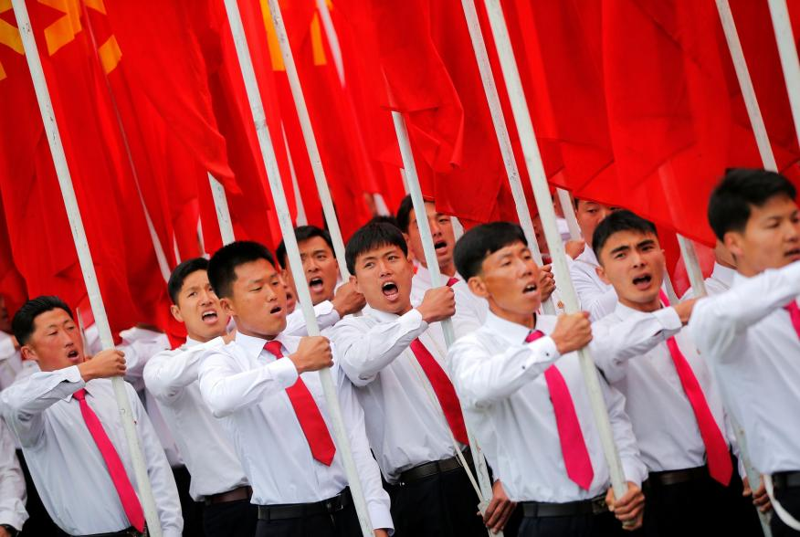 Students carrying party flags shout slogans as they march past North Korean leader Kim Jong Un during a mass rally and parade in the capital's main ceremonial square, a day after the ruling party wrapped up its first congress in 36 years by elevating him