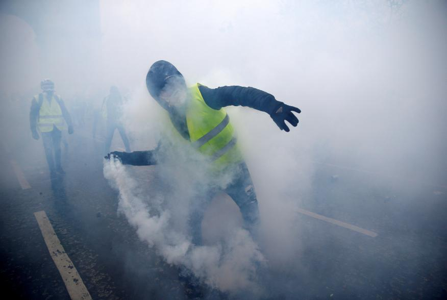 FILE PHOTO: Tear gas fills the air as a protester wearing a yellow vest, a symbol of a French drivers' protest against higher diesel taxes, demonstrates near the Place de l'Etoile in Paris, France, December 1, 2018. REUTERS/Stephane Mahe/File Photo