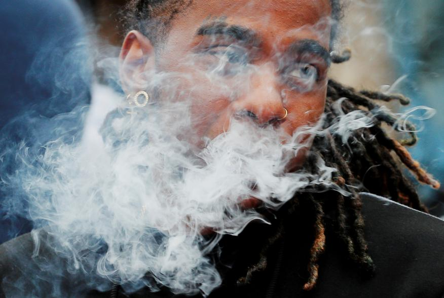A demonstrator vapes during a protest at the Massachusetts State House against the state's four-month ban of all vaping product sales in Boston, Massachusetts, U.S., October 3, 2019. REUTERS/Brian Snyder