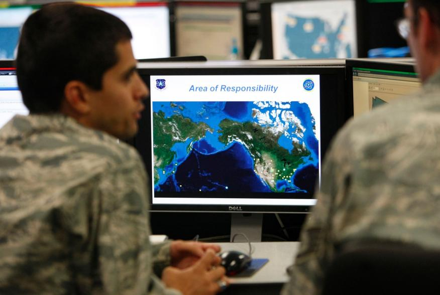 2Lt William Liggett (L) talks with a colleague as a map is displayed on one of the screens at the Air Force Space Command Network Operations & Security Center at Peterson Air Force Base in Colorado Springs, Colorado July 20, 2010. U.S. national security p