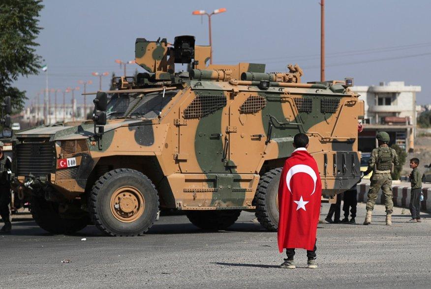 Αγόρι που φορά μια τουρκική σημαία στέκεται μπροστά από ένα τουρκικό στρατιωτικό όχημα στην πόλη Tal Abyad