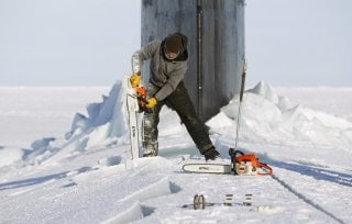 Applied Physics Laboratory Ice Station (APLS) employee Keith Magness uses a chainsaw to cut through ice on the hatches of the Seawolf class submarine USS Connecticut after the boat surfaced through Arctic sea ice during an exercise near the 2011 APLS camp