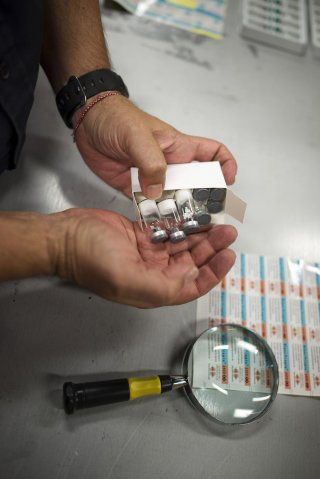U.S. Customs and Border Protection officer Boris Sapozhnikov looks at counterfeit drugs seized by the agency at its offices at John F. Kennedy Airport in New York August 15, 2012. REUTERS/Keith Bedford