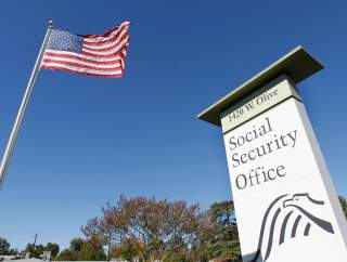 An American flag flutters in the wind next to signage for a United States Social Security Administration office in Burbank, California October 25, 2012. REUTERS/Fred Prouser