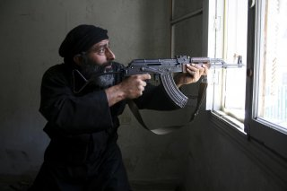 A Free Syrian Army fighter aims his AK-47 rifle through a window in Aleppo's Salaheddine neighbourhood April 28, 2013. Picture taken April 28, 2013. REUTERS/Aref Hretani