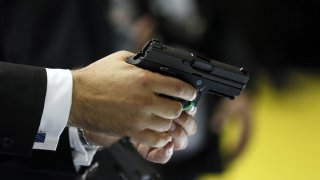 A man holds a Sig Sauer pistol during the Defence Security Equipment International (DSEI) arms fair at ExCel in London September 10, 2013. REUTERS/Stefan Wermuth