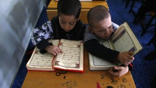 Uighur refugee boys read the Koran where they are housed in a gated complex in the central city of Kayseri, Turkey, February 11, 2015. REUTERS/Umit Bektas