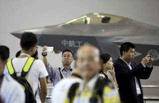A visitor takes a selfie in front of a model of J-31 stealth fighter at Aviation Industry Corporation of China (AVIC)'s booth at the Aviation Expo China 2015, in Beijing, China, September 16, 2015.