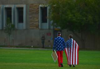 People wear the American flag as students and protesters gather at the