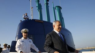 Israeli Prime Minister Benjamin Netanyahu (R) walks on the Rahav, the fifth submarine in the fleet, after it arrived in Haifa port January 12, 2016. REUTERS/Baz Ratner