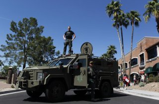 A Maricopa County, Arizona police SWAT team with an armored vehicle stand guard outside a campaign rally being held by Republican U.S. presidential candidate Donald Trump in Fountain Hills, Arizona March 19, 2016. REUTERS/Ricardo Arduengo