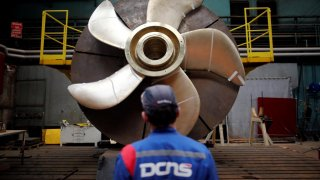 An employee looks at the propeller of a Scorpen submarine at the industrial site of the naval defence company and shipbuilder DCNS in La Montagne near Nantes, France, April 26, 2016. REUTERS/Stephane Mahe