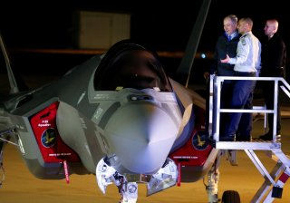 Israeli Prime Minister Benjamin Netanyahu stands next to a F-35 fighter jet just after it landed in Israel at Nevatim air base after the Israeli air force bought them at Nevatim