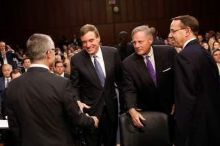Sen. Mark Warner (D-VA, 2-L) and Sen. Richard Burr (R-NC, 2-R) greet Acting FBI Director Andrew McCabe (L) and Deputy Attorney General Rod Rosenstein (R) as they arrive to testify before a Senate Intelligence Committee hearing on Capitol Hill