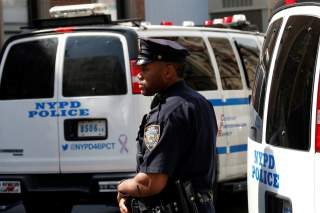 A New York City Police Department (NYPD) officer stands guard outside the 46th police precinct after a gunman fatally shot a female New York City police officer in an unprovoked attack early on Wednesday in the city's Bronx borough of New York City, U.S.,