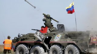 A serviceman from Venezuela fires an anti-aircraft missile with a Russian-made Igla ground-to-air launcher as he sits on top of an armoured personnel carrier (APC) during the Air defense battle masters competition as part of the International Army Games 2