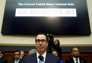 Treasury Secretary Steven Mnuchin sits under a display of the U.S. national debt as he testifies to the House Financial Services Committee on
