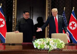 U.S. President Donald Trump and North Korea's leader Kim Jong Un (L) arrive to sign a document to acknowledge the progress of the talks and pledge to keep momentum going, after their summit at the Capella Hotel on Sentosa island in Singapore, June 12, 201