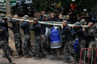 Military personnel carry a water pump machine as they enter the Tham Luang cave complex, where 12 boys and their soccer coach are trapped, in the northern province of Chiang Rai, Thailand, July 6, 2018. REUTERS/Athit Perawongmetha