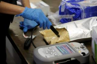 U.S. Customs and Border Protection officer Ella Olejnik uses an infrared machine to test a substance in a plastic bag at the International Mail Facility at O'Hare International Airport in Chicago, Illinois, U.S. November 29, 2017.
