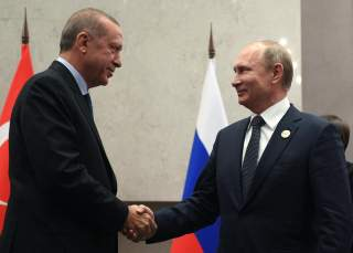 Russia's President Vladimir Putin (R) shakes hands with his Turkish counterpart Tayyip Erdogan during a meeting on the sidelines of the BRICS summit in Johannesburg, South Africa July 26, 2018. Sputnik/Vladimir Astapkovich/Kremlin