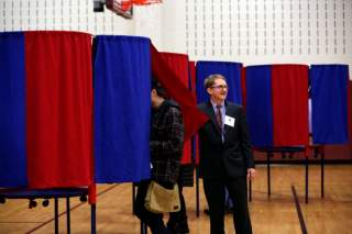 Election official Bill McClure assists voters at a polling place in Portsmouth, New Hampshire, U.S., November 6, 2018. REUTERS/Elizabeth Frantz