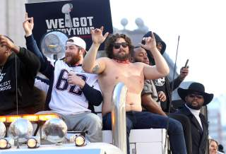 Feb 5, 2019; Boston, MA, USA; New England Patriots guard Joe Thuney (62) and center David Andrews , shirtless, ride a truck during the Super Bowl LIII championship parade.