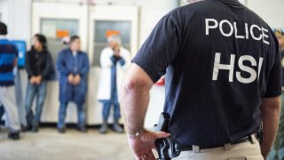 Image: HomelandSecurityInvestigations(HSI) officers from Immigration and Customs Enforcement (ICE) look on after executing search warrants and making some arrests at an agricultural processing facility in Canton, Mississippi, U.S. in this August 7, 201