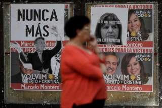 A woman stands near a wall covered in election posters one day after of the inauguration of Argentina's President Alberto Fernandez and his Vice President Cristina Fernandez de Kirchner in Buenos Aires, Argentina December 11, 2019. REUTERS/Ueslei Marcelin