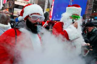 Revelers dressed as Santa Claus vape as they take part in the event called SantaCon at Times Square in New York City, U.S., December 14, 2019. REUTERS/Eduardo Munoz TPX IMAGES OF THE DAY