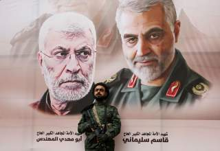 A Houthi militant stands by a billboard with posters of Iraqi militia commander Abu Mahdi al-Muhandis and Iranian military commander Qassem Soleimani during a rally by Houthi supporters to denounce the U.S. killing of both commanders, in Sanaa, Yemen