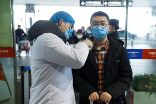 A medical official takes the body temperature of a man at the departure hall of the airport in Changsha, Hunan Province, as the country is hit by an outbreak of a new coronavirus, China, January 27, 2020. REUTERS/Thomas Peter
