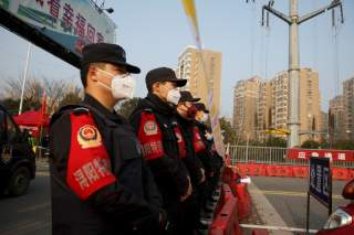 Police stand at a checkpoint at the Jiujiang Yangtze River Bridge that crosses from Hubei province in Jiujiang, Jiangxi province, China, as the country is hit by an outbreak of a new coronavirus, January 31, 2020.