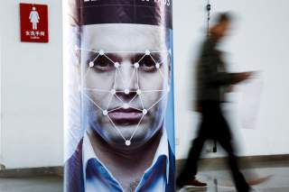 A man walks past a poster simulating facial recognition software at the Security China 2018 exhibition on public safety and security in Beijing, China October 24, 2018. REUTERS/Thomas Peter