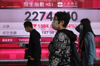 People wear protective masks as they walk past a panel displaying the Hang Seng Index during morning trading, following the outbreak of the new coronavirus in Hong Kong, China, March 13, 2020. REUTERS/Tyrone Siu