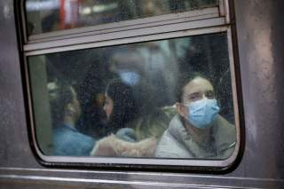 A woman wears a face mask on the subway as the coronavirus outbreak continued in Manhattan, New York City, New York, U.S., March 13, 2020. REUTERS/Andrew Kelly