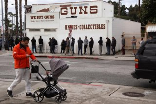 A pedestrian pushes a stroller as people wait in line outside to buy supplies at the Martin B. Retting, Inc. gun store amid fears of the global growth of coronavirus cases, in Culver City, California, U.S. March 15, 2020. REUTERS/Patrick T. Fallon