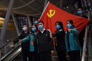 Medical workers from outside Wuhan pose for pictures with a Chinese Communist Party flag at the Wuhan Railway Station before leaving the epicentre of the novel coronavirus disease (COVID-19) outbreak, in Hubei province, China March 17, 2020. Picture taken