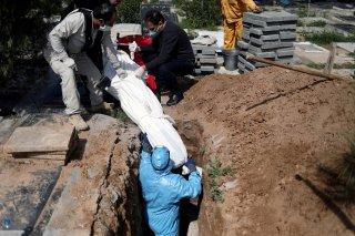 Iranian men bury the journalist Abdollah Zavieh, who passed away due to coronavirus disease (COVID-19), at Behesht Zahra cemetery in Tehran, Iran, March 24, 2020. WANA (West Asia News Agency)/Ali Khara via REUTERS