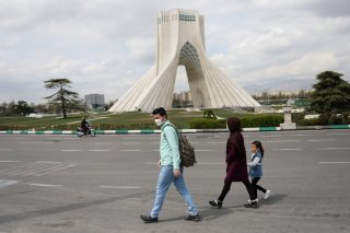 A family wear protective face masks and gloves, amid fear of coronavirus disease (COVID-19), as they walk by the iconic Freedom Square, in Tehran, Iran March 26, 2020. WANA (West Asia News Agency)/Ali Khara via REUTERS