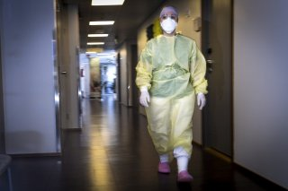 A nurse wearing protective equipment walks at a clinic in Vantaa, Finland March 26, 2020. Lehtikuva/Emmi Korhonen via REUTERS