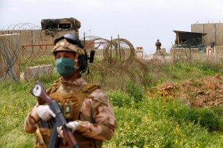An Iraqi soldier wears a protective face mask and gloves, following the outbreak of coronavirus disease (COVID-19), as he stands guard during the hand over of Qayyarah Airfield West from US-led coalition forces to Iraqi Security Forces