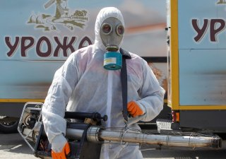 A specialist with protective gear sanitizes the facilities of a local bakery to prevent the spread of coronavirus disease (COVID-19) in the rebel-controlled city of Donetsk, Ukraine March 27, 2020. The logos on the trucks read