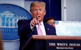U.S. President Donald Trump addresses the daily coronavirus response briefing as Defense Secretary Mark Esper listens at the White House in Washington, U.S., April 1, 2020. REUTERS/Tom Brenner