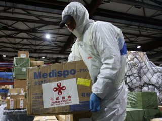 A worker carries a box while unloading a shipment of medical and protective gear sent from China to help the fight against coronavirus disease (COVID-19) outbreak at Almaty International Airport, Kazakhstan April 2, 2020. REUTERS/Pavel Mikheyev