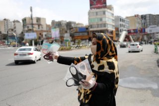 A woman wears a protective face mask and gloves, amid fear of the coronavirus disease (COVID-19), as she sells the masks in Tajrish square in Tehran, Iran April 2, 2020. WANA (West Asia News Agency)/Ali Khara via REUTERS
