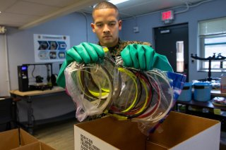 U.S. Marine Corps Cpl. Michael Espinosa packs 3-D printed face masks for health workers treating coronavirus disease (COVID-19) into a box at Camp Lejeune, North Carolina, U.S. March 30, 2020. Picture taken March 30, 2020. U.S. Marine Corps/Lance Cpl. Sco