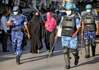 Veiled Muslim women walk past members of Rapid Action Force (RAF) patrolling a neighborhood during a lockdown in the area after dozens of men were taken to a quarantine facility amid concerns about the spread of coronavirus disease (COVID-19)