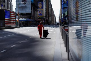A Times Square Alliance street sweeper worker walks though a nearly empty Times Square in Manhattan during the outbreak of the coronavirus disease (COVID-19) in New York City, New York, U.S., April 7, 2020. REUTERS/Mike Segar